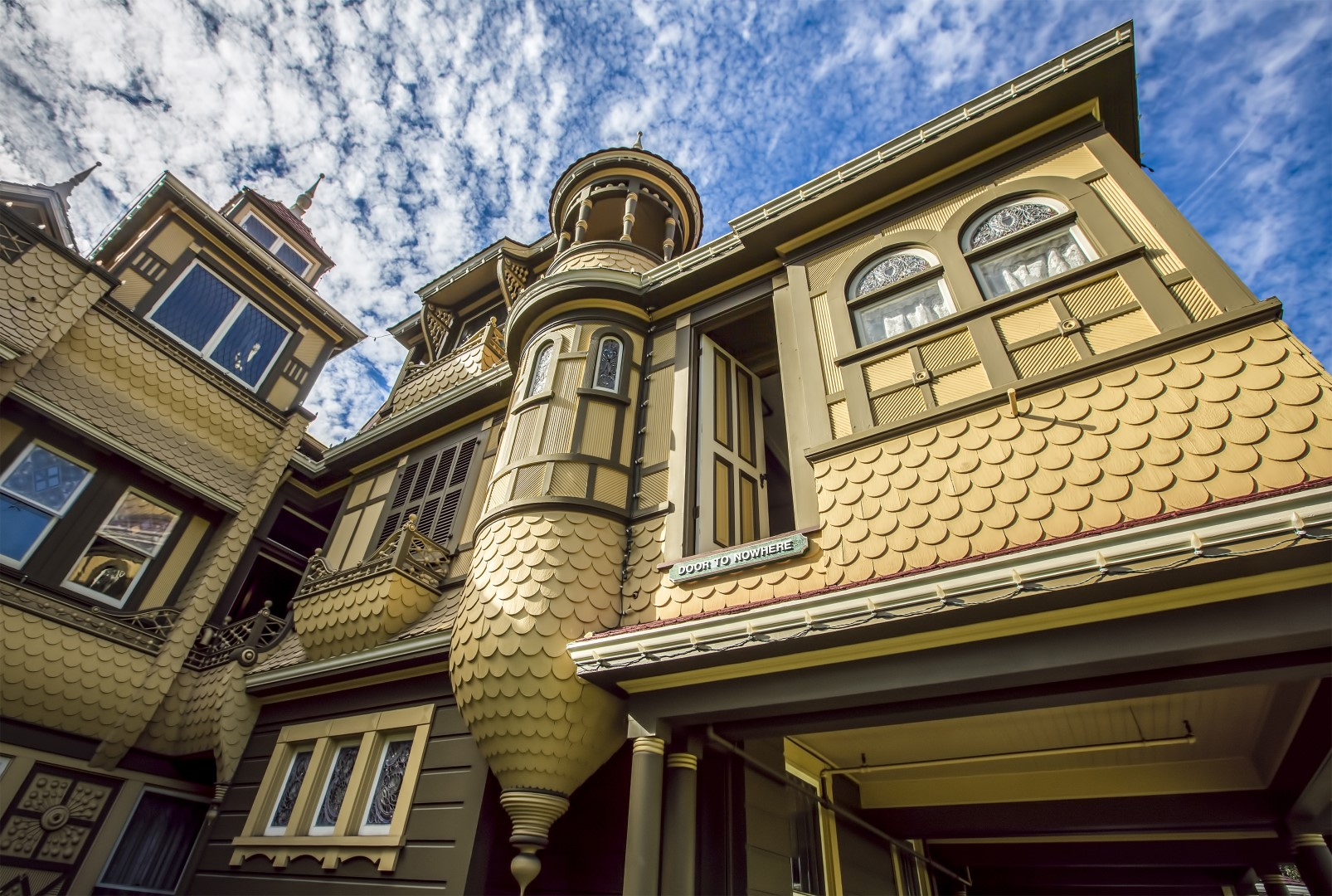 bigs Winchester Mystery House looking up at facade with blue sky clouds Large